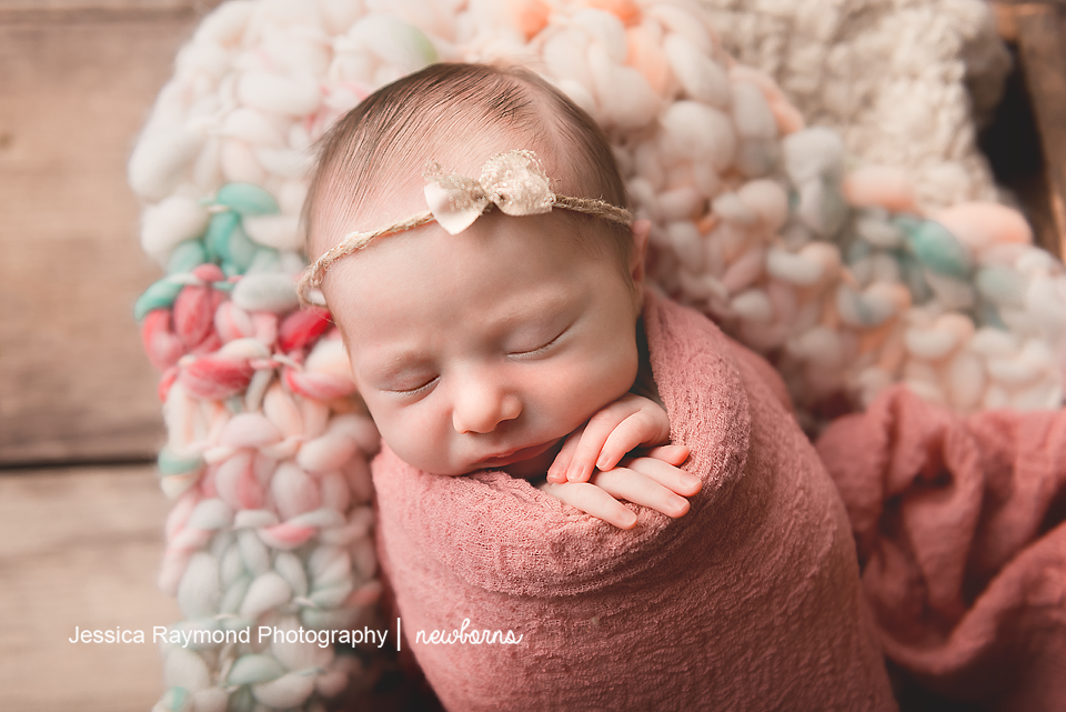 newborn baby photographer san diego california newborn photo shoot girl wrapped in pink with headband