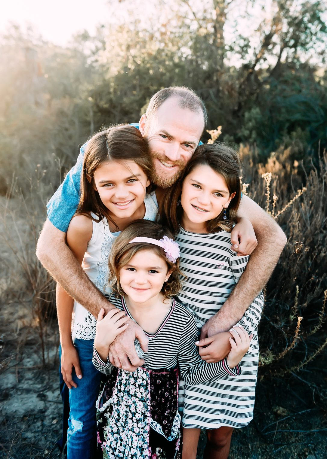 family pictures in a field dad with three daughters