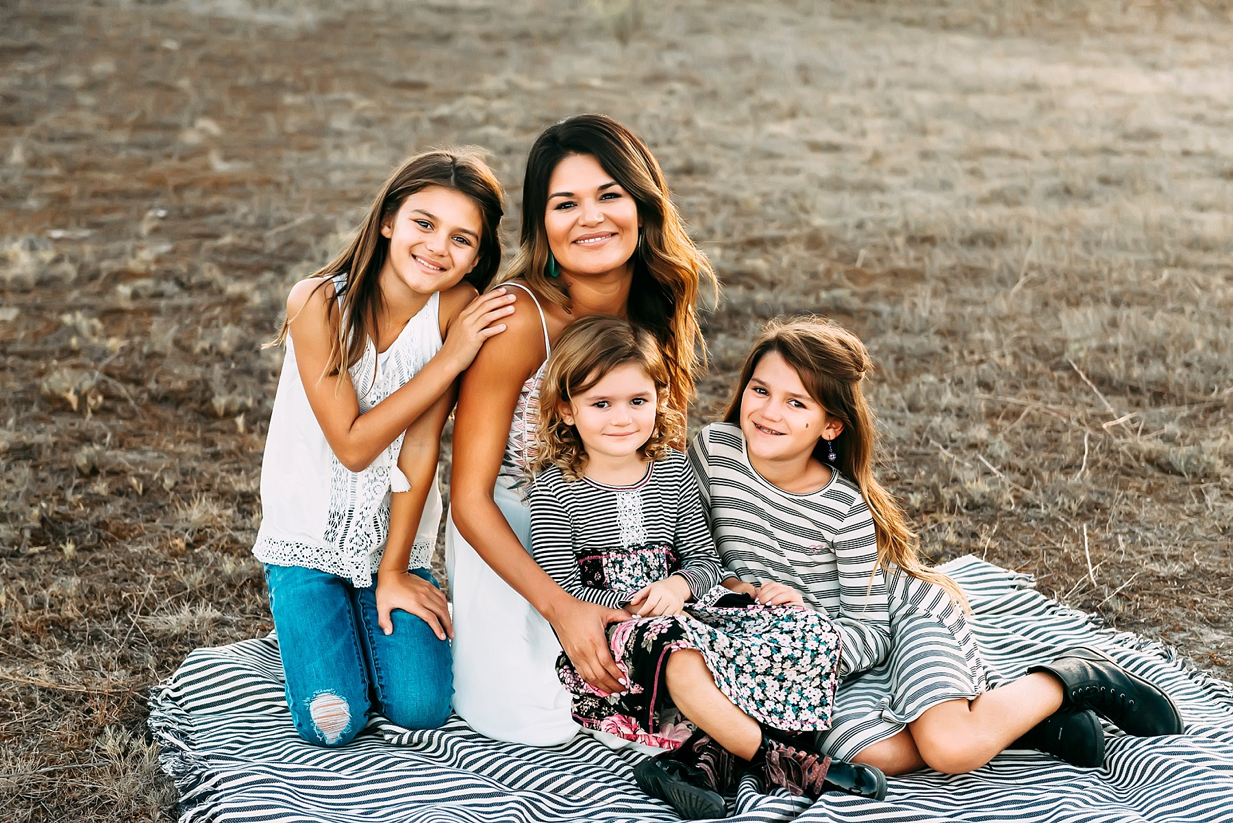 family pictures in a field mom with kids pose