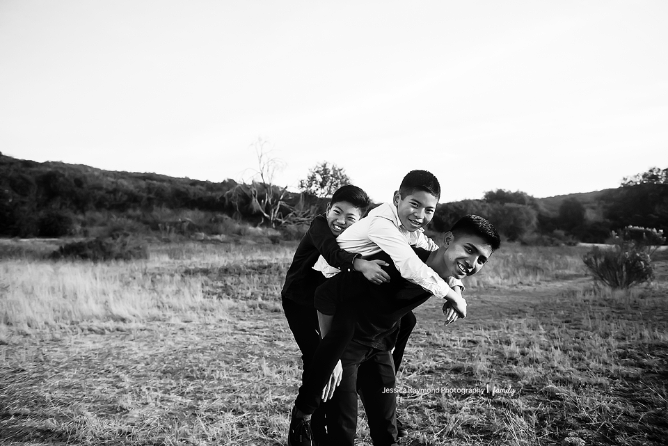 san elijo family photographer family photos family portrait session 3 brother in field giving piggy back rides