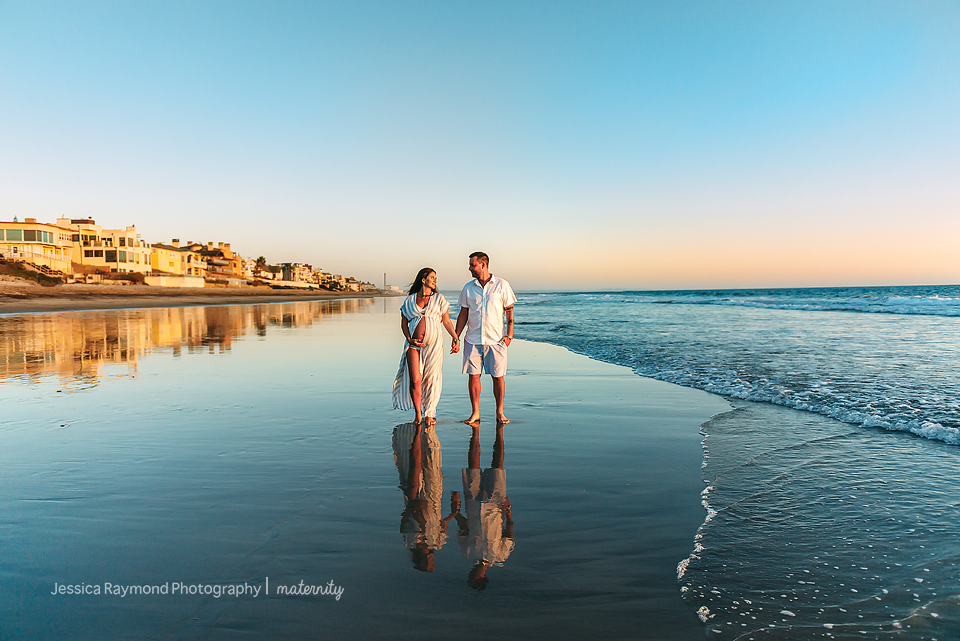 beach maternity pictures elegant couple pose walking on beach