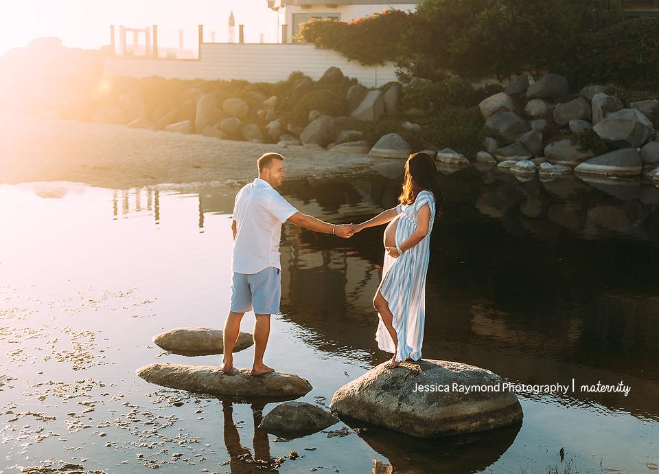 beach maternity pictures elegant couple pose on rocks