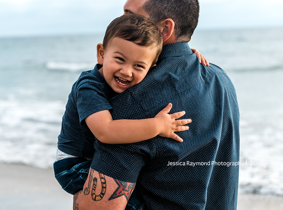 family photography oceanside best family photographer dad holding son on beach