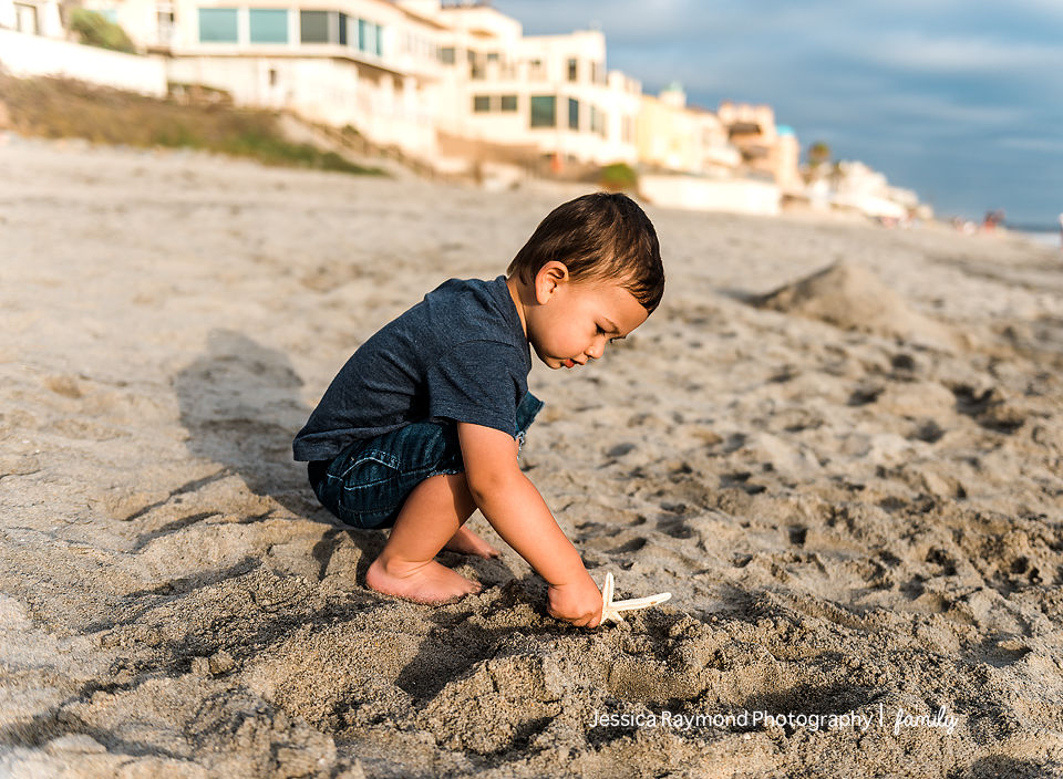 family photography oceanside family photographer boy playing in sand at beach