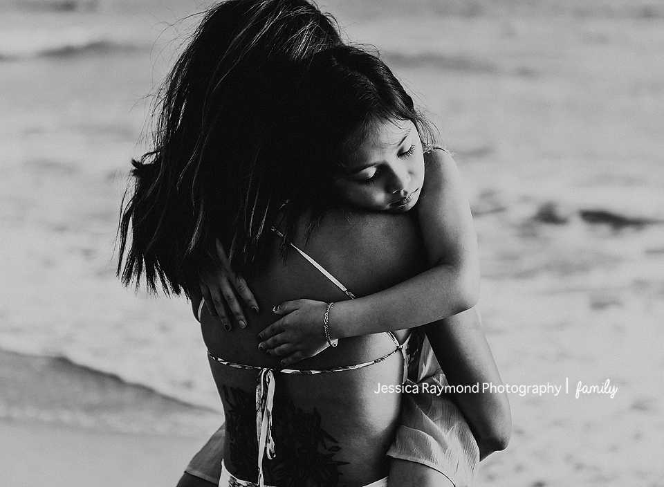 family photography oceanside family photographer mom holding daughter on beach