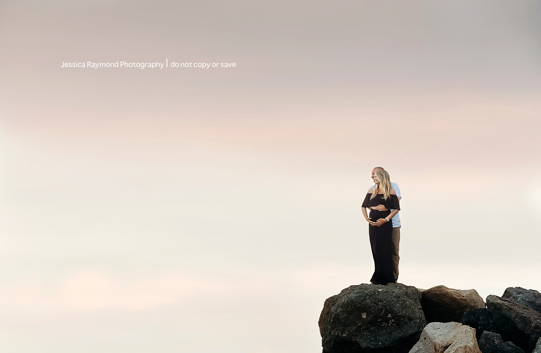 maternity beach picture ideas couple pose on rocks