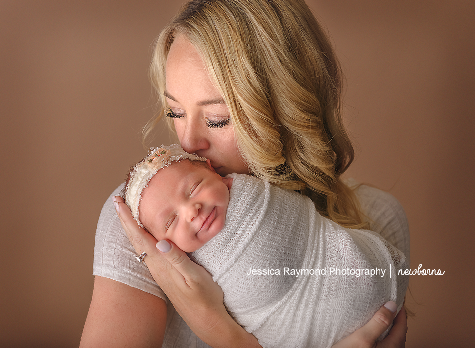 carlsbad baby photographer newborn family session newborn photo shoot baby girl in moms arms smiling