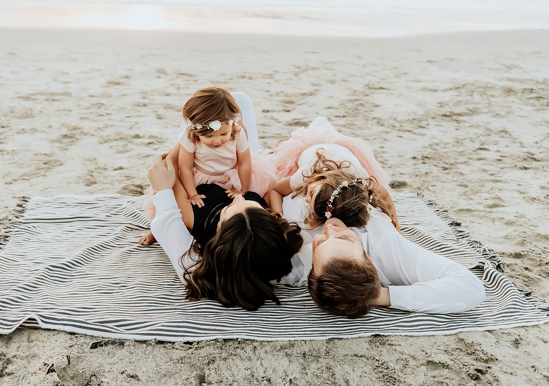 family of 4 beach pictures cuddling on blanket