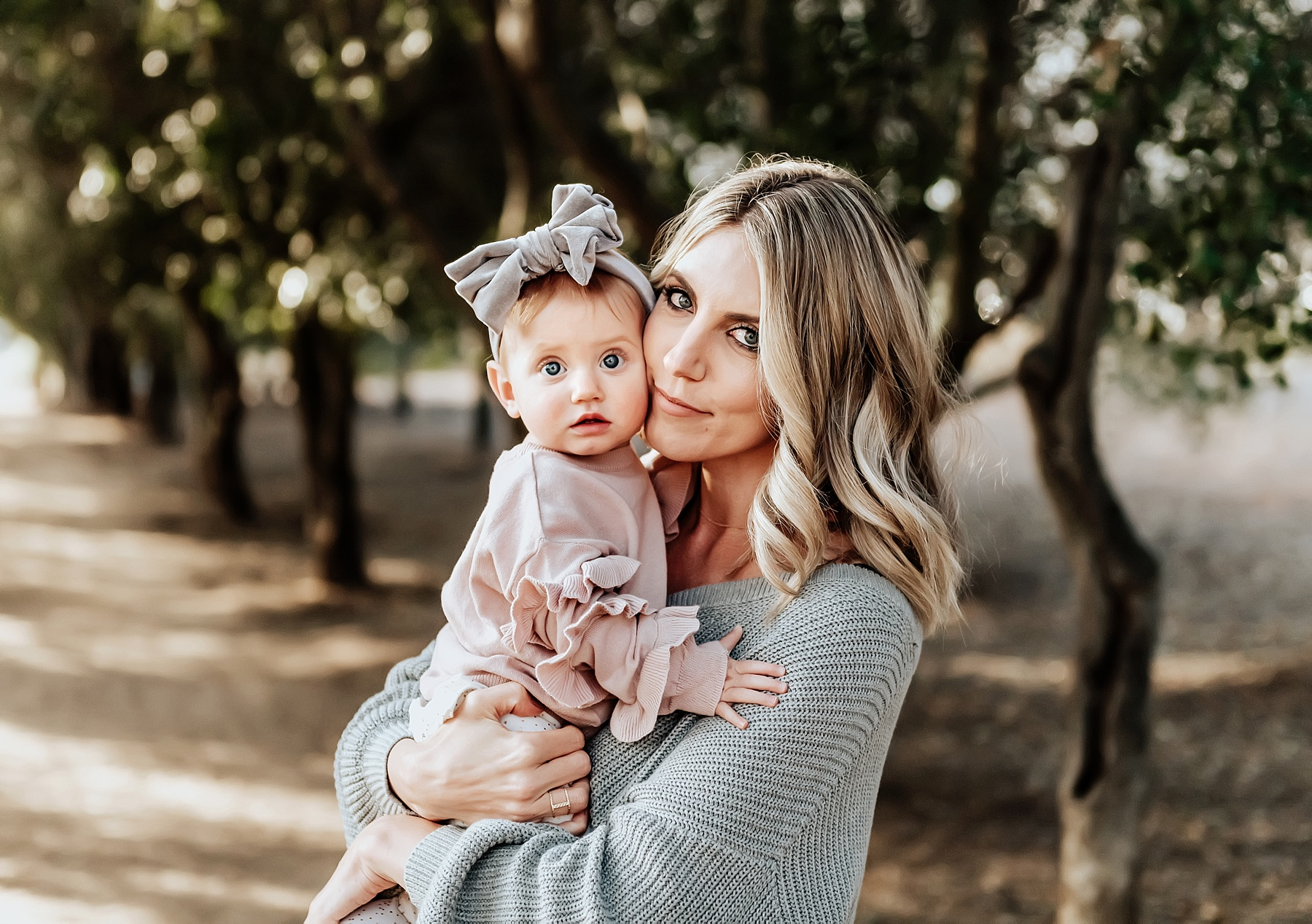 family portraits san diego mom holding daughter under trees