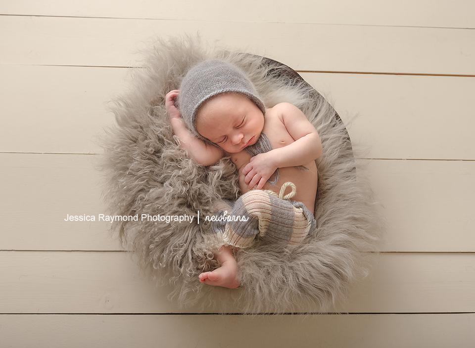 newborn photoshoot san diego newborn posing newborn boy in basket with grey beanie and grey fur