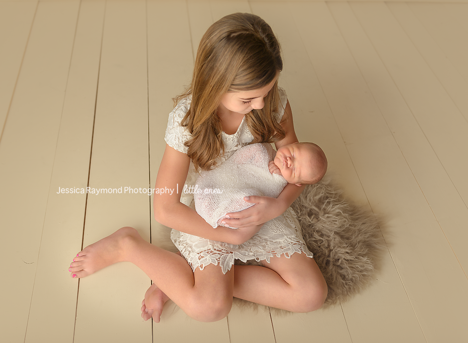 best newborn photographers sister holding baby brother