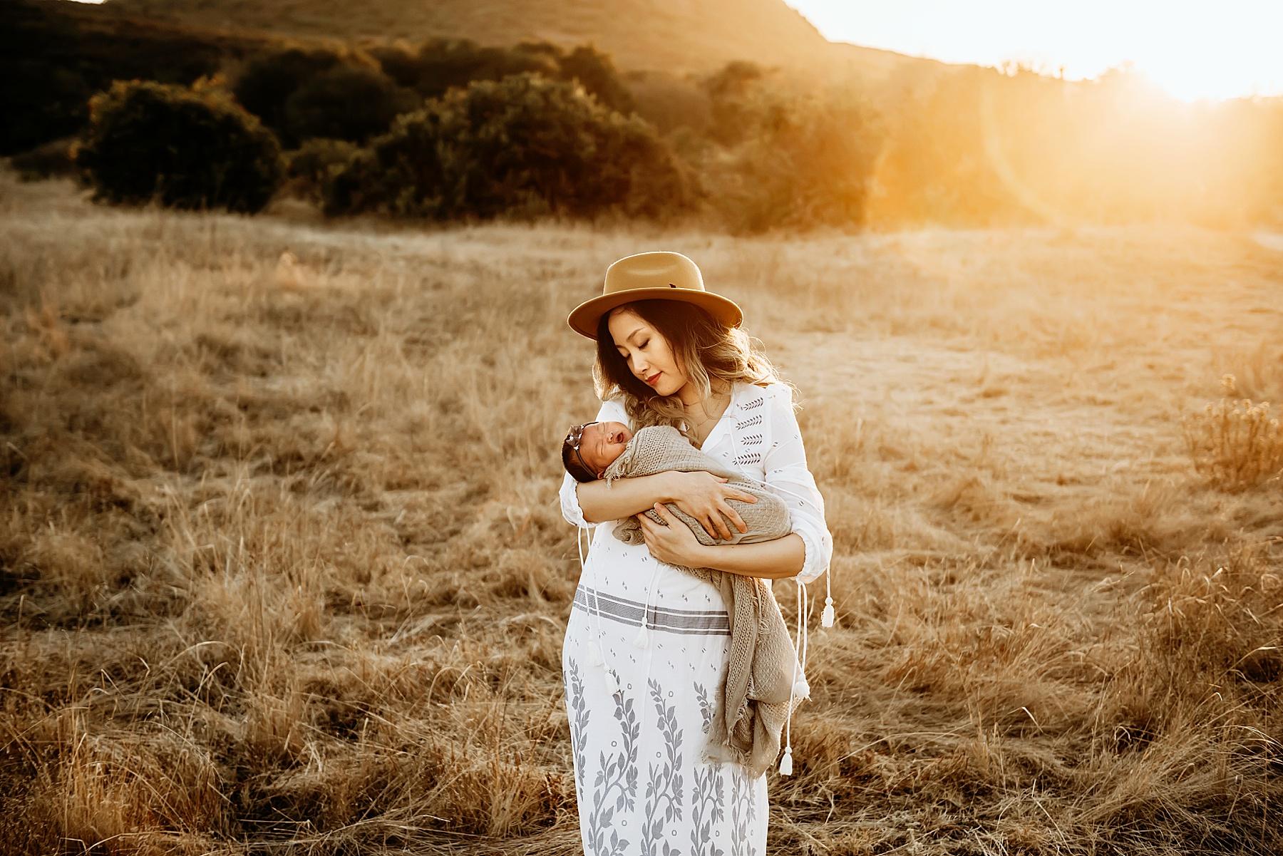 newborn pictures in open field mom baby girl