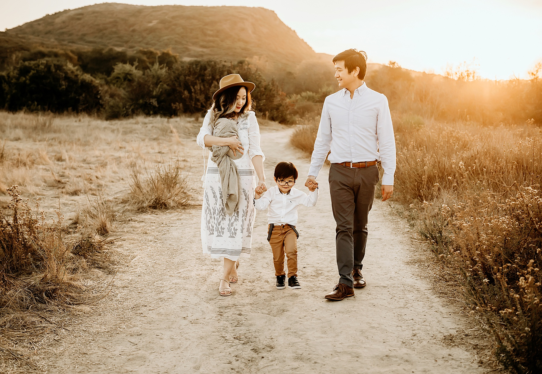 newborn pictures in open field family walking