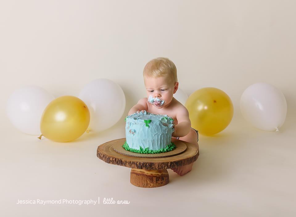 one year old portraits cake smash birthday session carlsbad california birthday boy digging into blue cake