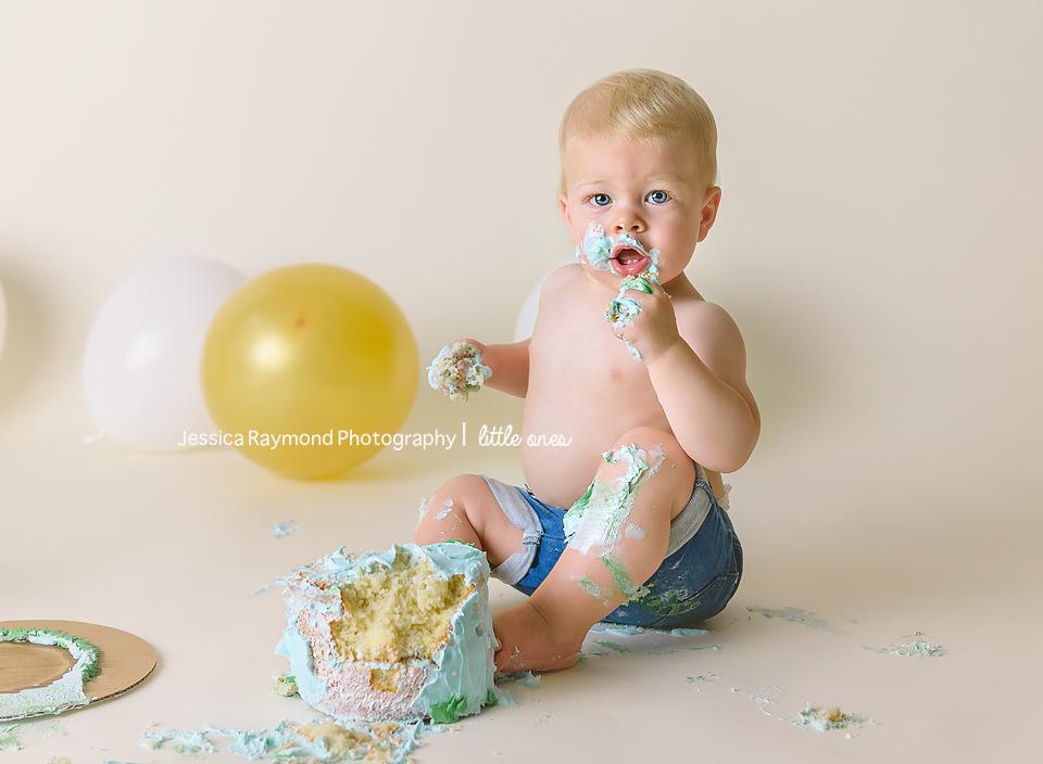 one year old portraits cake smash birthday session carlsbad california birthday boy eating blue cake