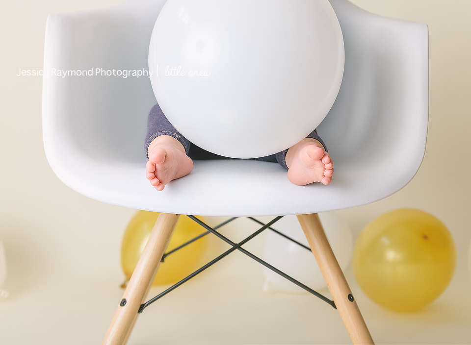 one year old portraits cake smash birthday session carlsbad california birthday boy holding balloon close up of toes