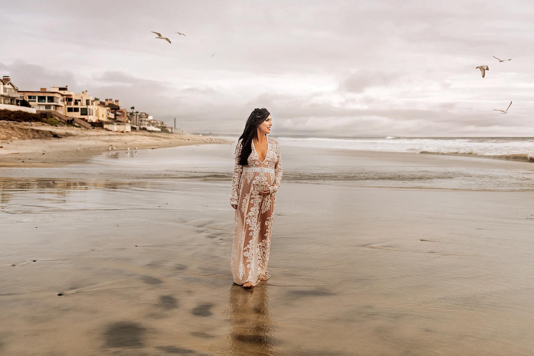 pregnant mom walking on beach