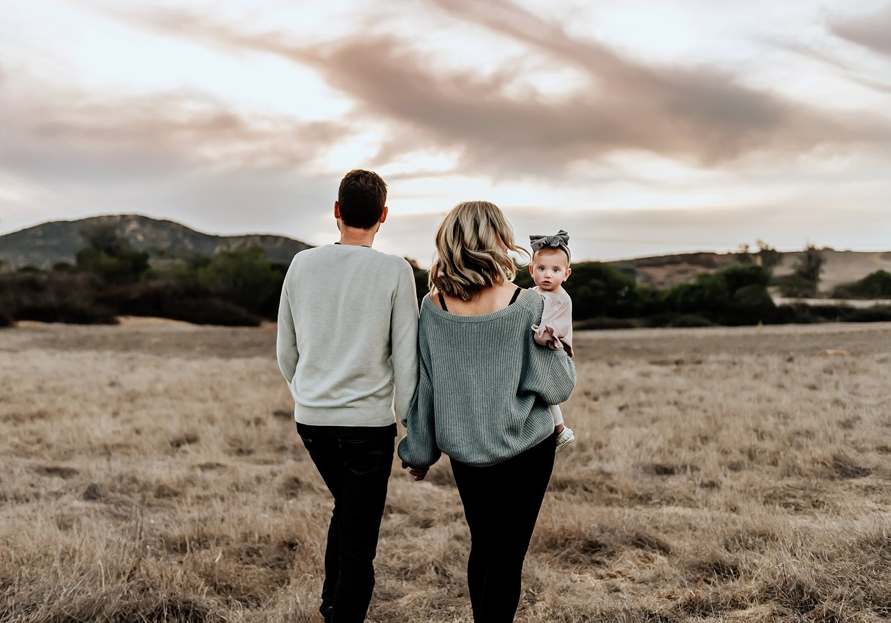 san diego family photographer family of three walking in field