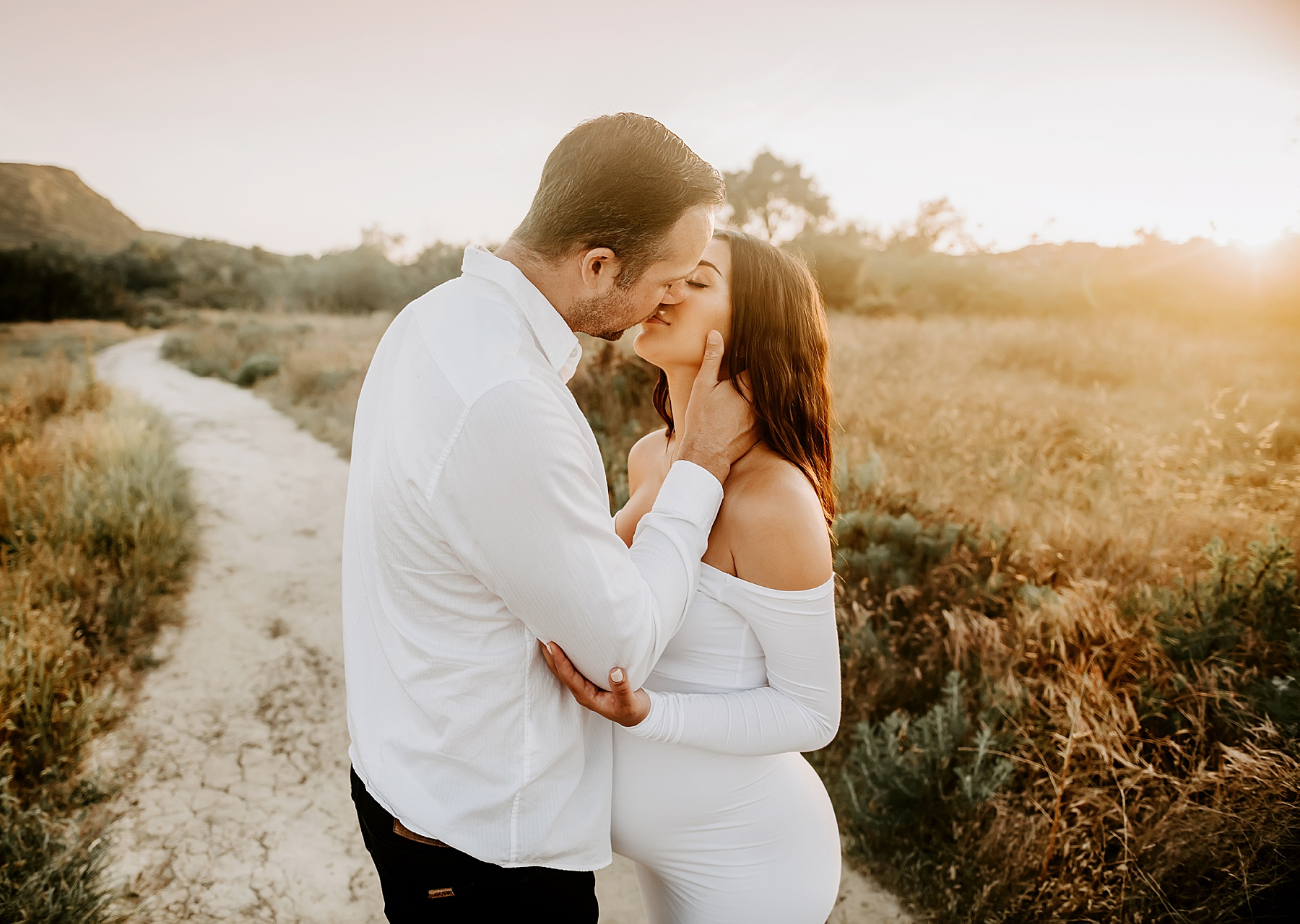 sunset field maternity session couple kissing