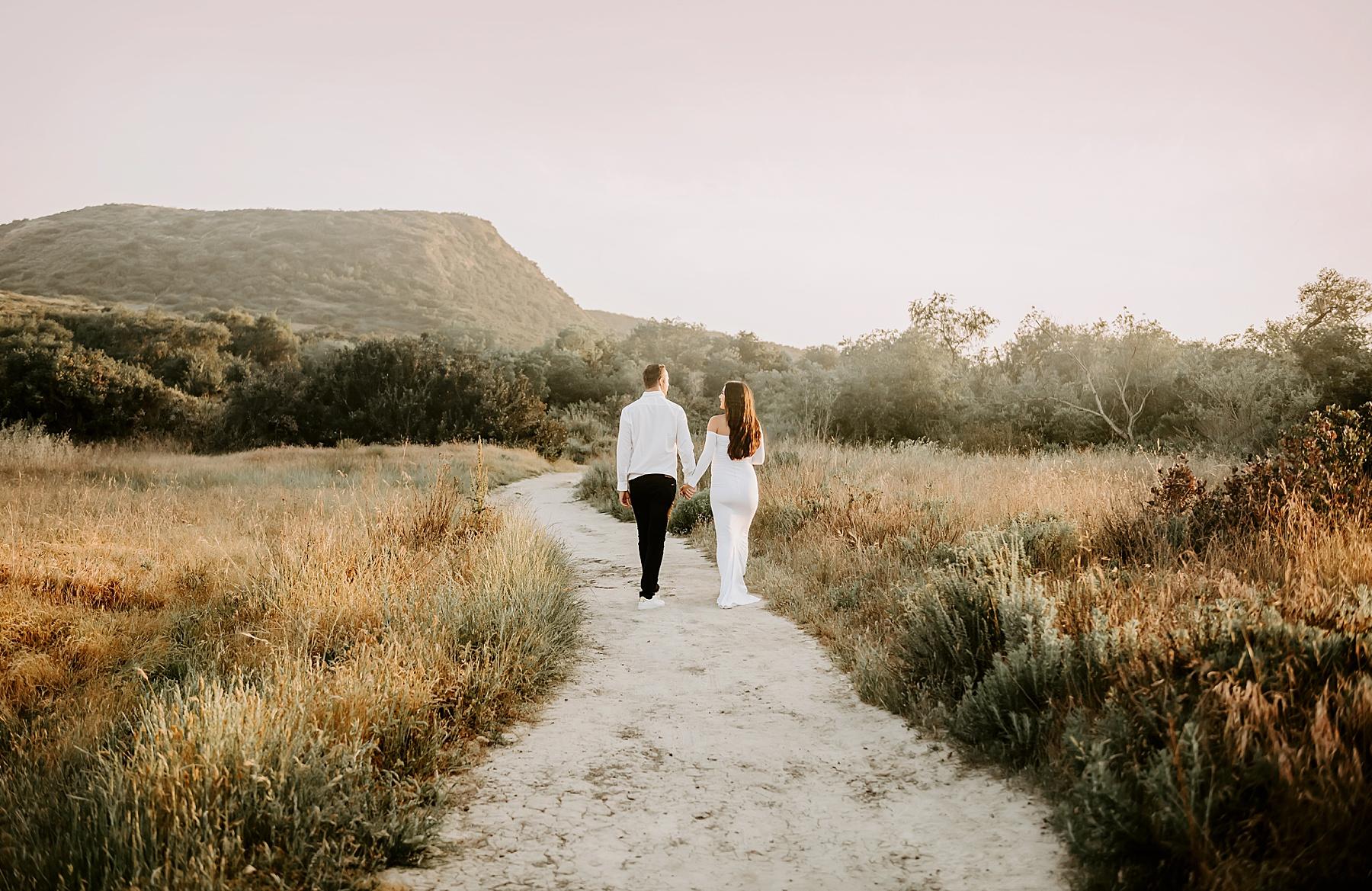 sunset field maternity session couple walking