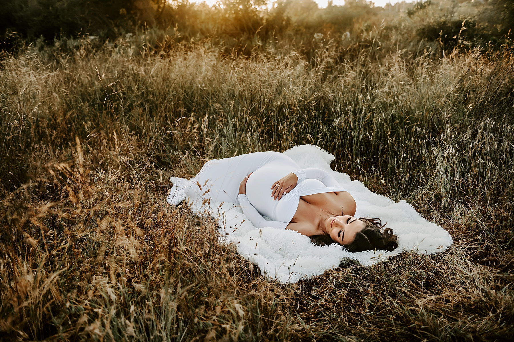 sunset field maternity session laying on white blanket